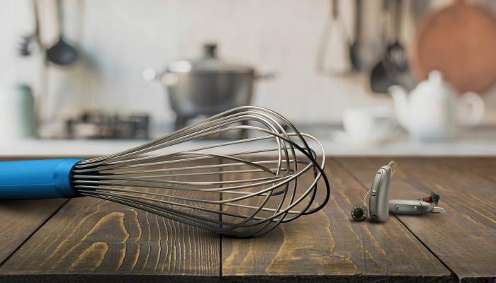 Unitron: Zwei Hörgeräte und ein Quirl in einer Küchenumgebung
