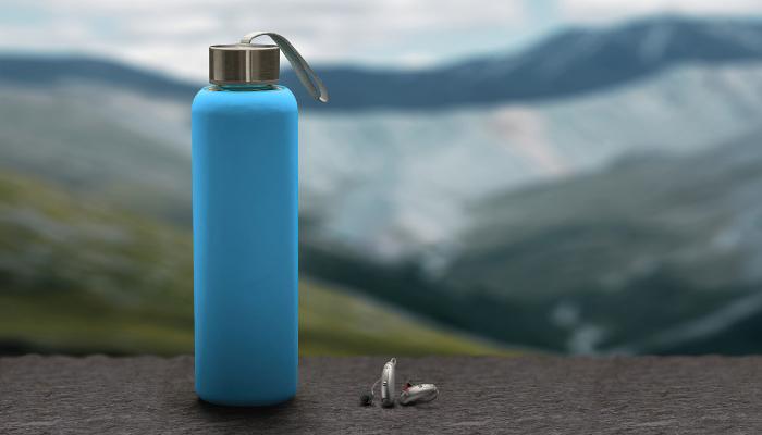 Unitron: Hörgeräte und eine Trinkflasche in einer Berglandschaft