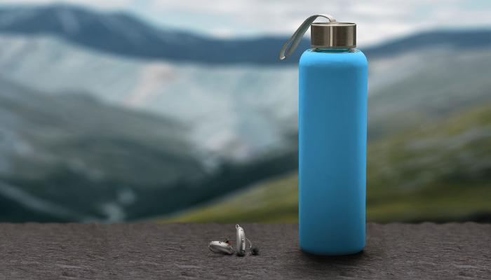 Unitron: Eine Trinkflasche und zwei Hörgeräte in einer Berglandschaft