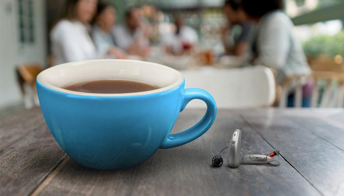 Unitron: Zwei Hörgeräte und eine Kaffeetasse