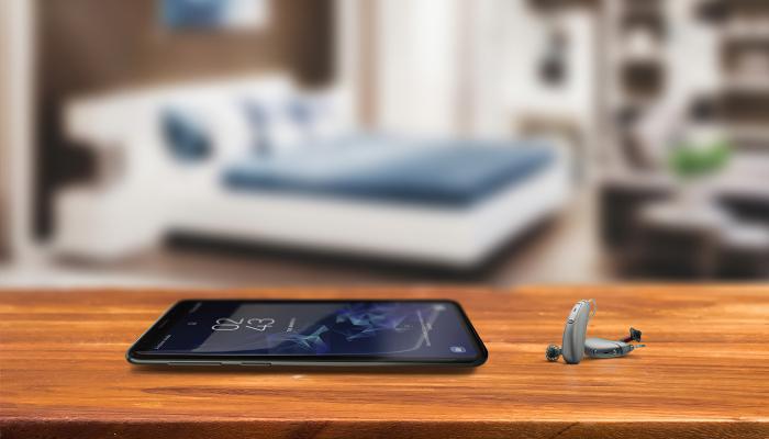 Unitron: Hörgeräte neben einem Smartphone