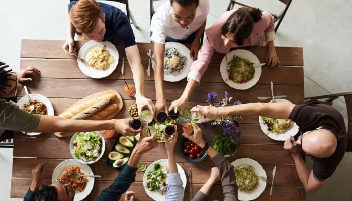 Unitron: Essen in Gesellschaft, Tisch von oben, alle stoßen an