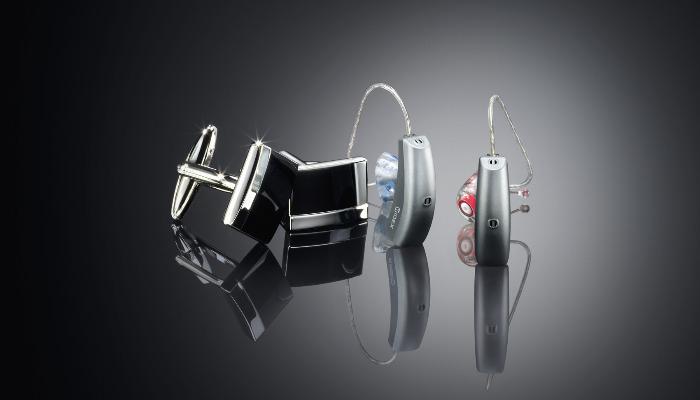 Widex: Zwei Hörgeräte neben zwei Manschettenknöpfen