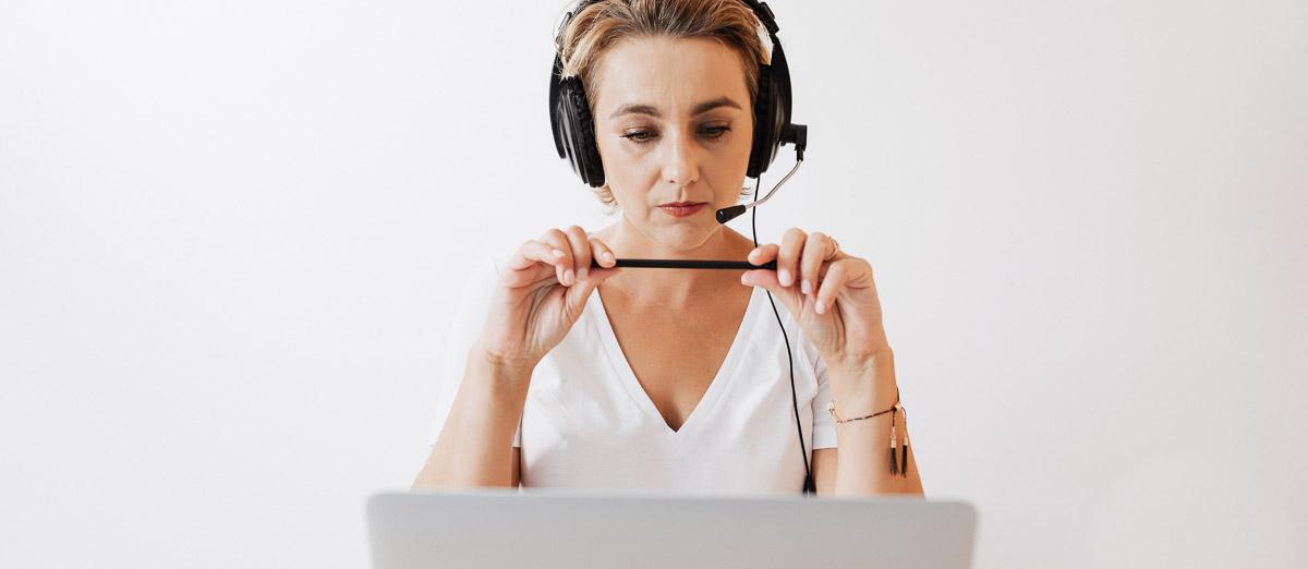Hörgeräte-Ferneinstellung, Frau mit Kopfhörer vor einem Laptop