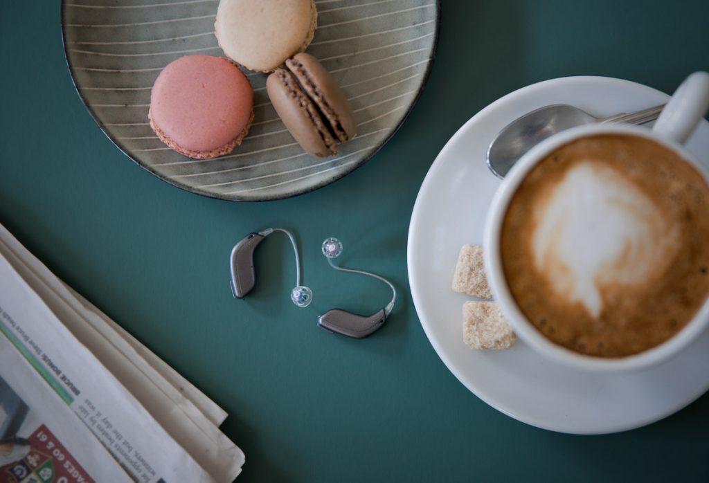 Oticon OPN S Hörgeräte auf einem Kaffeetisch