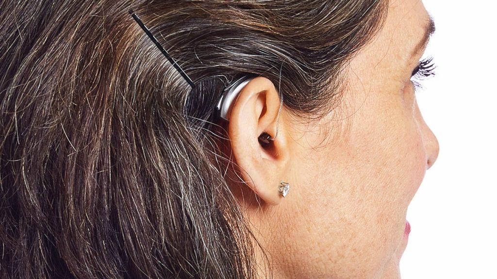 Silbernes Hinter-dem-Ohr-Hörgerät an einem Frauenohr
