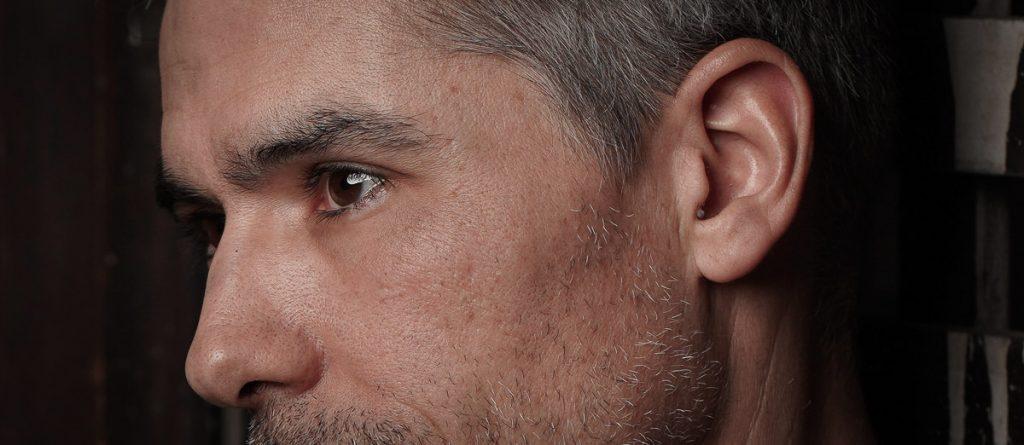 Mann mit unsichtbaren Hörgeräte, Großaufnahme von Gesicht und Ohr