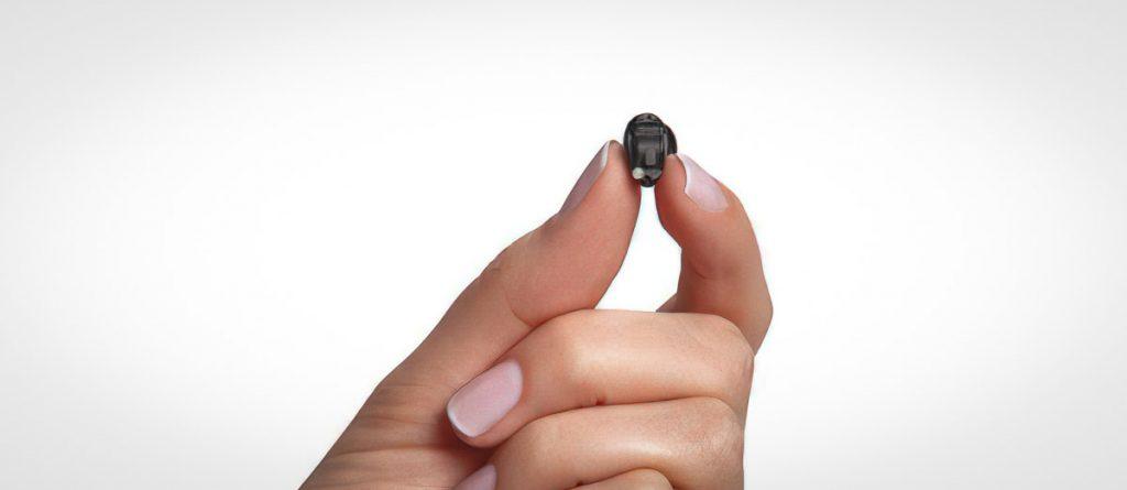 Winziges Hörgerät zwischen zwei Fingern