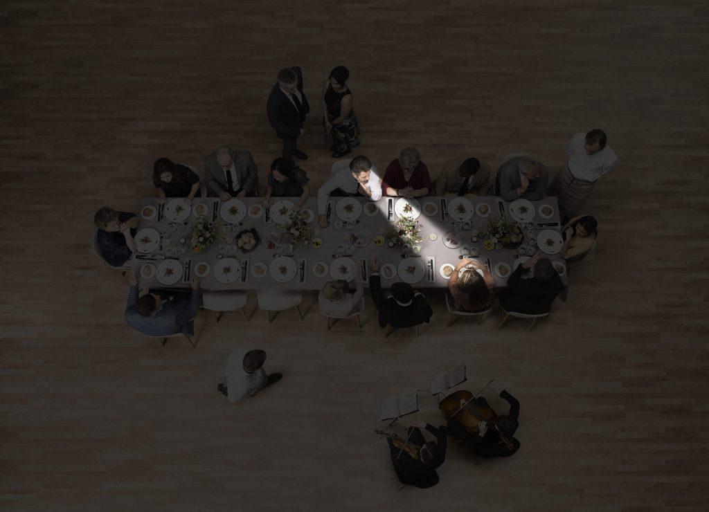 Blick von oben auf einen Tisch mit vielen Menschen. Ein Zuhörer schaut schräg gegenüber einen Gesprächspartner an. Die Ausrichtung der Richtmikrofone wird durch ein Spotlight symbolisiert.