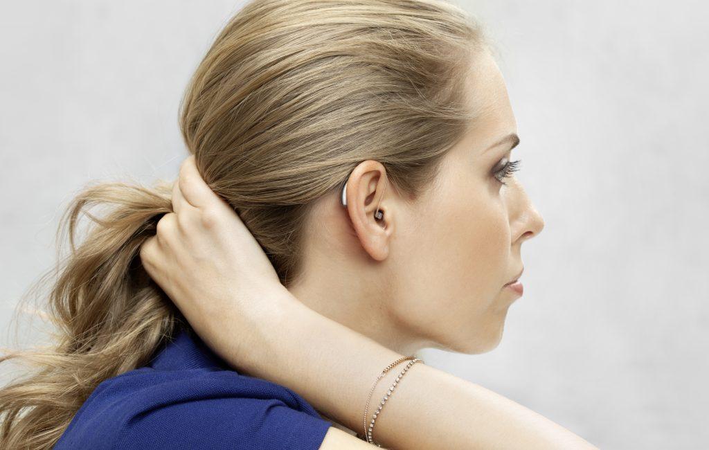 Blonde Frau von der Seite mit Exhörer-Hörgerät im Ohr