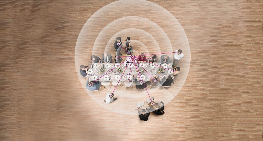 Blick von oben auf einen langen Tisch, an dem mehrere Menschen sitzen. Schallwellen und Linien symbolisieren die Arbeitsweise von Richtmikrofonen.