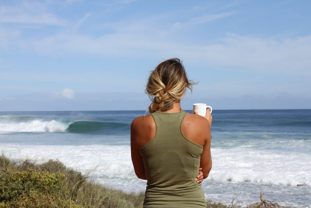Frau schaut aufs Meer und lauscht den Wellen