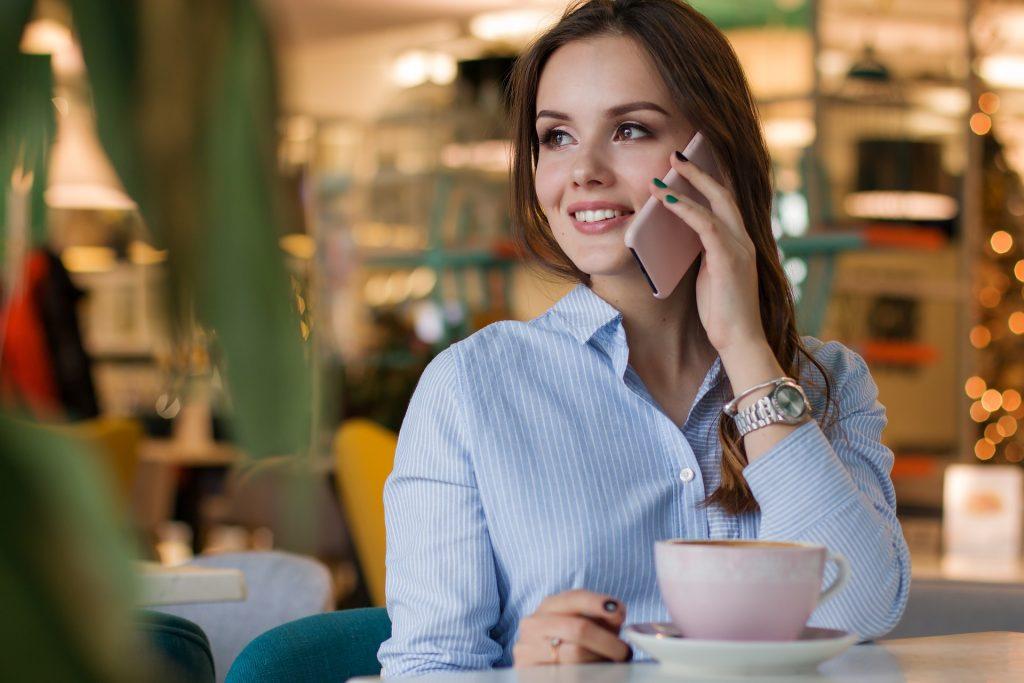 Frau sitzt im Café und telefoniert