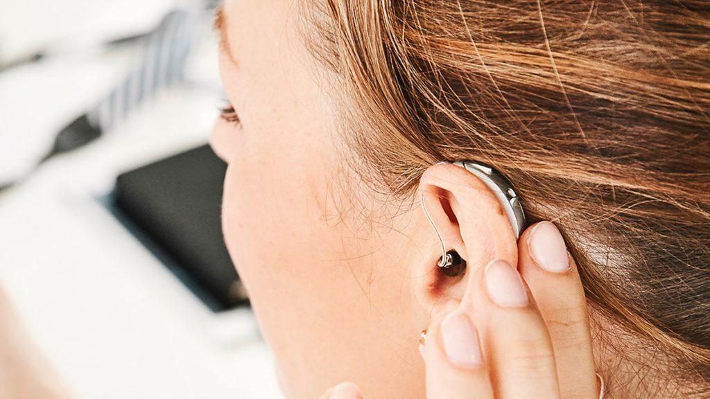 Frau berührt ein Hansaton Excite Pro Hörgerät